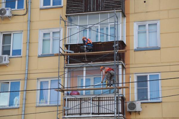 Заказчики этих работ по остеклению балконов теперь в зоне риска. Фото: Мария Ленц / Комсомольская правда